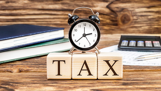 """Word """"Tax"""" with clock on the office workplace. Business concept."""